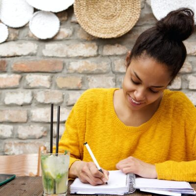 Beautiful young black woman writing notes at cafe