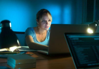 Beautiful woman working late at night in office, surfing the web and writing post on social network with laptop computer. The girl is concentrated and serious